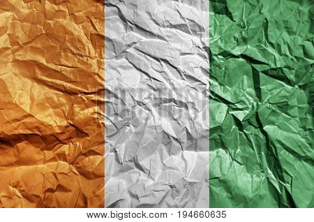 Cote d'lvoire flag painted on crumpled paper background