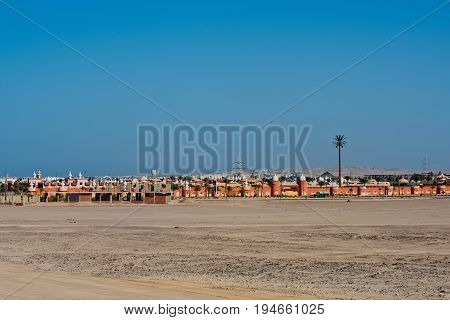 Desert resort hotel with defensive wall towers and buildings in sand dunes on sunny day on blue sky background. Summer vacation and holidays. Travel and travelling. Wanderlust
