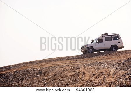 Car driving on desert hill on sand road on white sky background. Dune bashing. Safari trip on jeep. Offroad adventure. Extreme activity. Travel travelling. Summer vacation