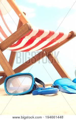 Snorkeling mask and flippers under deckchair on beach