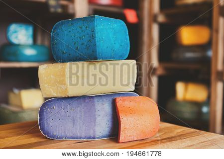 Cheese Mix. Gouda pesto lavender, blue, violet and red at cheese grocery shop background