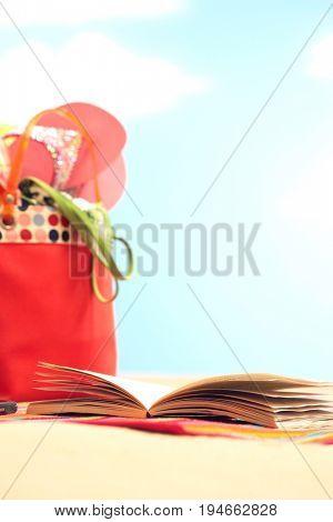 Open book next to beach bag on beach close up