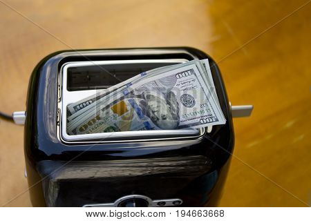 US dollars roasting in toaster closeup studio photo concept of life expenses