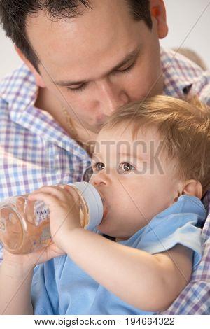 Father feeding baby boy kissing his head.