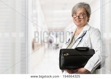 Mature female doctor standing on hospital corridor, holding bag, looking at camera, smiling.
