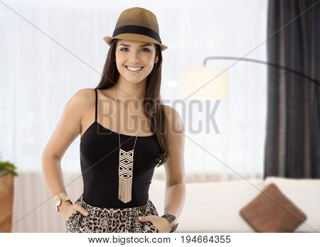 Trendy woman in hat standing with hands on hip at home smiling into camera.