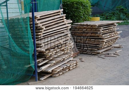 Stacked old wooden pallets near construction site.