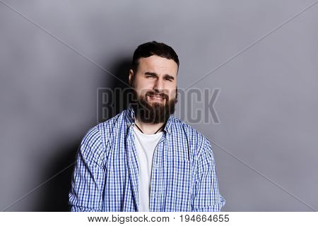 Bearded man expressing disgust on face, grimacing on camera, gray studio background. Negative emotions