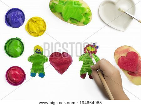 childs hand play painting with potatoes stamps in red green yellow and purple prints are a hart and a man shape poster paints and brush some isolated objects on a white background