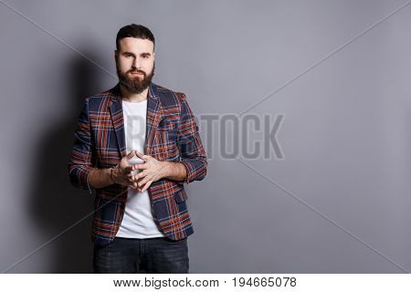 Bearded man with public speaker gesture. Fingers connected at fingertips, pose which imposes power and patience, gray studio background