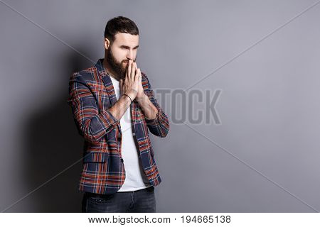 Portrait of hopeful bearded hipster praying. Young guy holding hands clasped near face, looking away, gray studio background, copy space