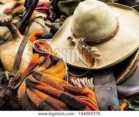 Vintage cowboy's hat with feather lays across a horse blanket saddle and other aging western equipment
