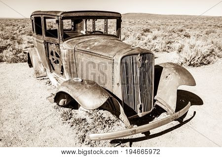 A sepia toned black and white image of a rusted antique car with wheels and other parts missing abandoned in a desert landscape
