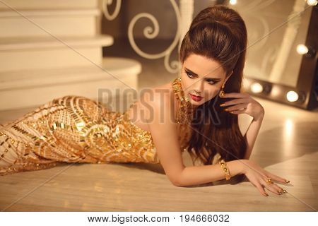 Elegant Fashion Brunette Woman In Luxury Golden Dress. Hair Style And Red Lips Makeup. Manicured Nai