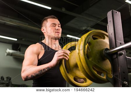 Smiling power. Young sportsman preparing his barbell by twisting power disk in.