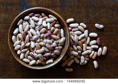 Dry Pinto Beans In Dark Wooden Bowl Isolated On Dark Brown Wood From Above. Spilled Beans.