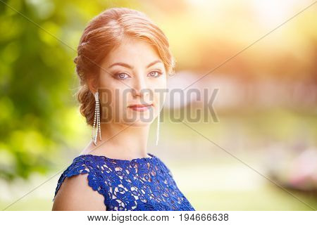 Young beautiful girl in blue lace dress looking straight into camera. Outdoor portrait of young elegant woman at the park