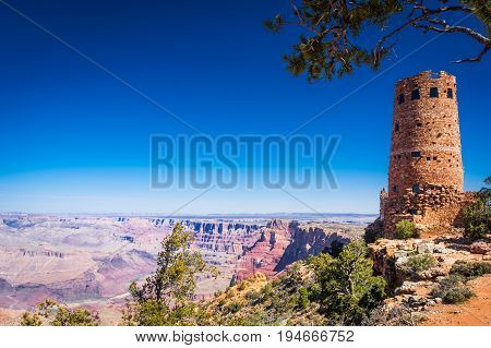 Landscape of the rim of the Grand Canyon with pine shrubs and the Desert View Watchtower in the foreground and a clear blue sky in the background