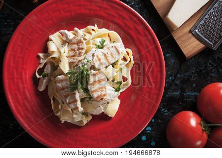 Italian fettuccine alfredo pasta with grilled chicken meat