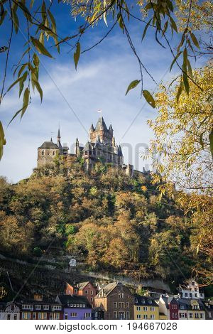 An image of Cochem's homes and the town's Medieval castle overhead with willows in the foreground