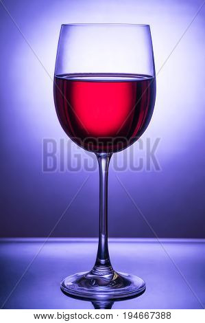 Beautiful glass with red wine up to the light in front of a blue light spot