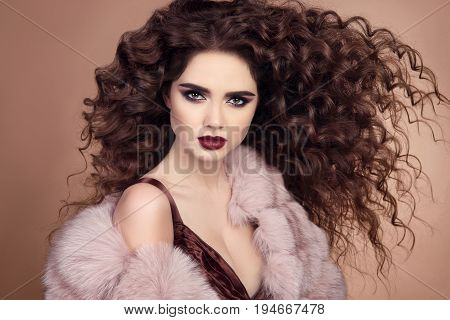 Curly Hairstyle. Fashionable Elegant Woman With Makeup And Blowing Healthy Long Hair Posing In Pink