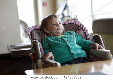 Boy sitting on high chair in cafe