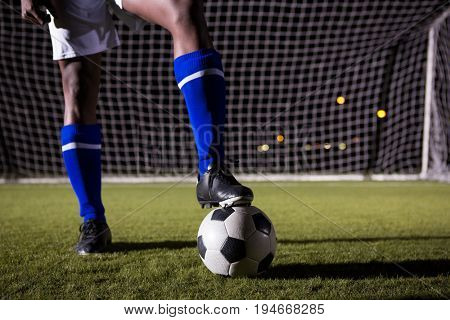 Low section of male soccer player standing with ball against goal post on playing field