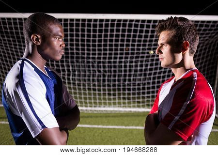 Side view of young male soccer players looking at each other standing against goal post