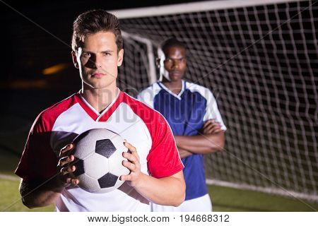 Portrait of confident soccer player holding ball with rival athlete standing against goal post
