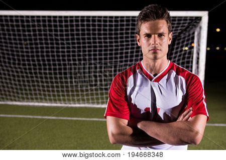 Portrait of confident young male soccer player standing with arms crossed against goal post on playing field
