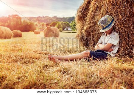 Boy leaning and sleeping against a haystack on a lazy summer evening at sunset
