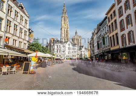 Street view with Our Lady church tower in the center of Antwerpen city, Belgium. Long exposure image technic with motion blurred people and clouds