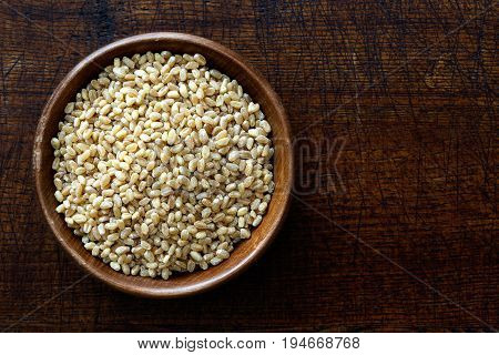 Spelt Groats In Dark Wooden Bowl Isolated On Dark Brown Wood From Above.