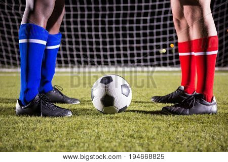 Low section of male players standing by soccer ball against goal post on playing field at night