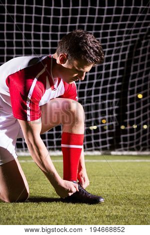 Young male soccer player tying shoelace against goal post on soccer field