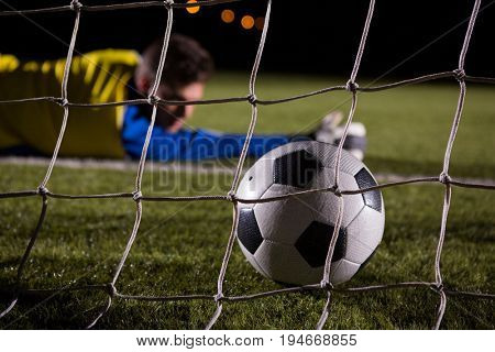 Close-up of soccer ball in goal post against goalkeeper lying on field