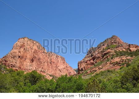 Crescent moon between hills in Kolob Canyons in Zion National Park, in the northwest corner of the park, narrow parallel box canyons are cut into the western edge of the Colorado Plateau.