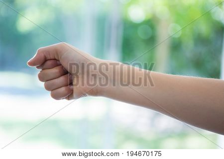 Cropped image of hand clenching fist against window