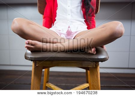 Low section of girl sitting with crossed legged on chair at home