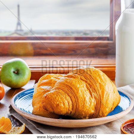 Classic French food for healthy breakfast. Plate of fresh croissants fruit jam and milk on a rustic wooden table Paris landscape on background. European traditional food tour in France.