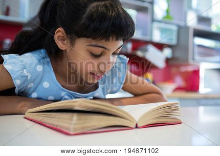 Close-up of girl reading novel in kitchen at home