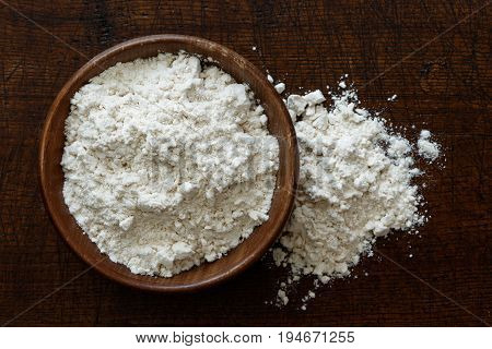 Fine White Flour In Dark Wooden Bowl Isolated On Dark Brown Wood From Above. Spilled Flour.