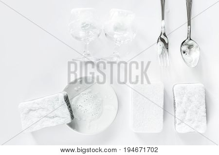 Sponge and tableware on white background top view.