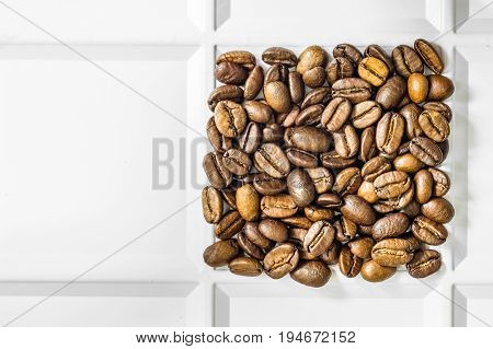 Roasted coffee beans arabica laid out square in a white tray. Grocery background with copyspace.