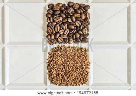 Roasted coffee beans arabica and granules of freeze-dried instant coffee laid out in the form of a square on a white tray. Grocery background with copyspace.