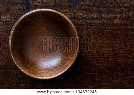 Empty Dark Wooden Bowl Isolated On Dark Brown Wood From Above.