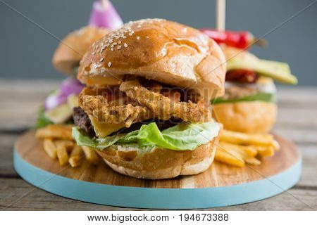 Close up of onion rings in burger on cutting board
