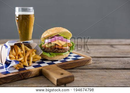 Close up of meal served with beer on cutting board at table against wall