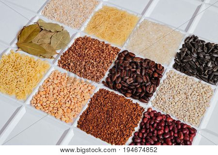 Set of groceries laying horizontal perspective: barley grits vermicelli rice sunflower seeds bay leafs buckwheat roasted coffee beans pearl barley figured macaroni dried peas freeze-dried instant coffee dried seeds of beans.